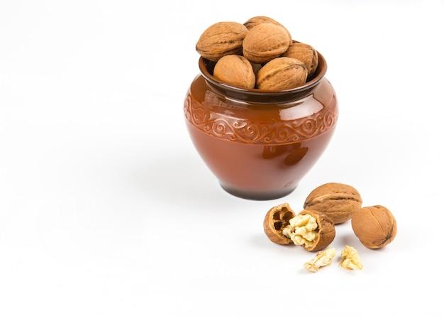 Apra il primo piano delle noci in vaso marrone su fondo bianco