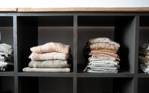 Armadio aperto con tanti vestiti piegati armadio organizzato con vestiti accatastati moderno e pulito in...