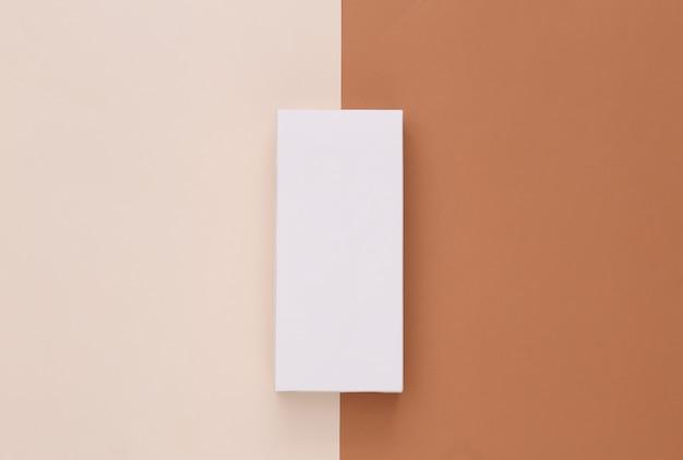 Scatola di imballaggio bianca aperta su beige marrone. minimalismo