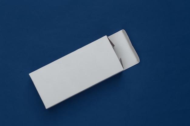 Scatola di imballaggio bianca aperta sul blu classico. minimalismo