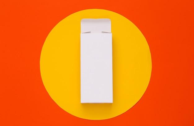 Scatola di imballaggio bianca aperta sull'arancione con cerchio giallo. minimalismo