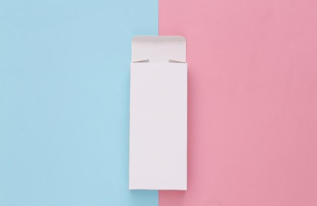 Scatola di imballaggio bianca aperta su pastello blu rosa. minimalismo