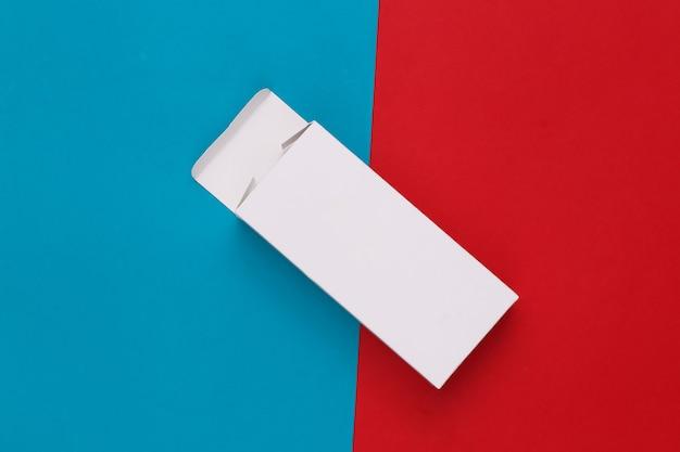 Scatola di imballaggio bianca aperta su blu rosso. minimalismo