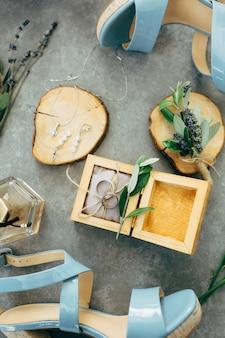 Una scatola di legno aperta con fedi nuziali su sfondo grigio e scarpe da damigella d'onore blu