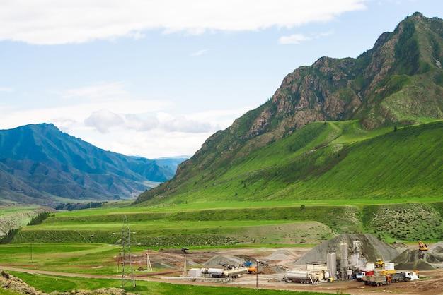 Miniere e cave a cielo aperto in montagna. industria pesante negli altopiani. macchinari al lavoro.