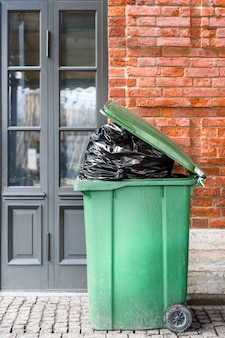 Pattumiera di plastica verde grande aperta con i sacchetti pieni della spazzatura. eliminazione di rifiuti
