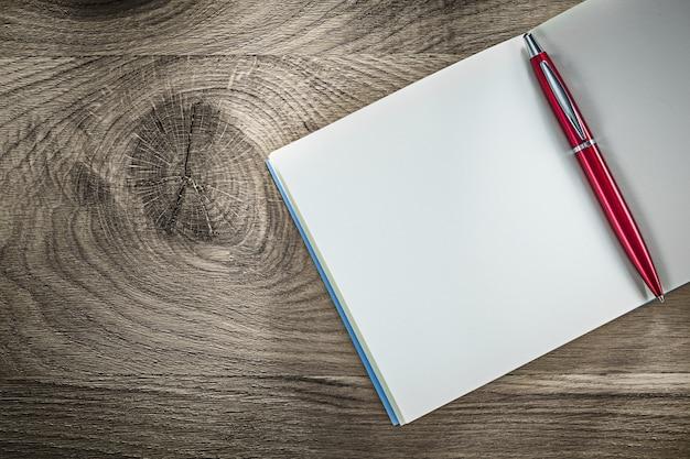 Penna a sfera aperta del taccuino in bianco sulla tavola di legno