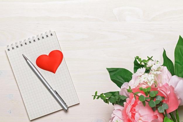 Blocco note, penna, cuore e fiori in bianco aperti su di legno.
