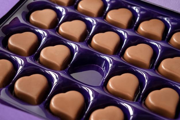 Scatola aperta di cioccolatini a forma di cuore con una cella vuota. celebrazione di san valentino