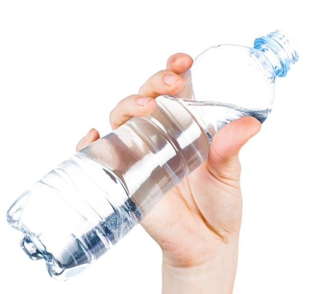 Bottiglia di plastica aperta dell'acqua potabile in mano femminile sulla superficie bianca isolata