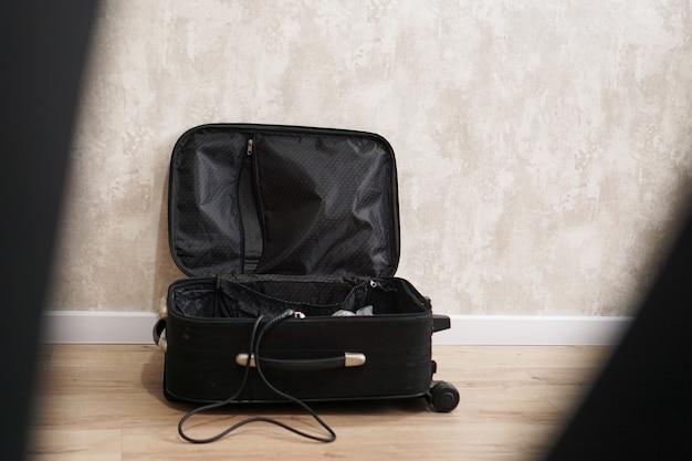 Valigia vuota e nera aperta per cose diverse su sfondo grigio. concetto di preparazione al viaggio
