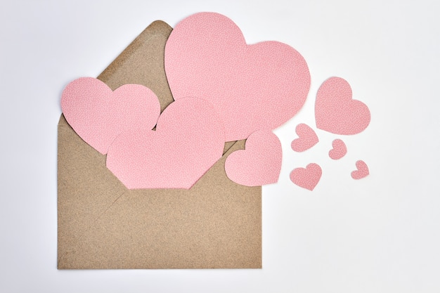 Busta aperta e cuori di carta rosa. busta di san valentino da carta artigianale e cuori decorativi su sfondo bianco. esprimi il tuo amore con la lettera.