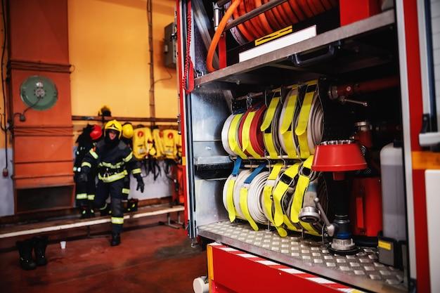 Camion dei pompieri aperto con tubi flessibili e vigile del fuoco che si prepara all'azione