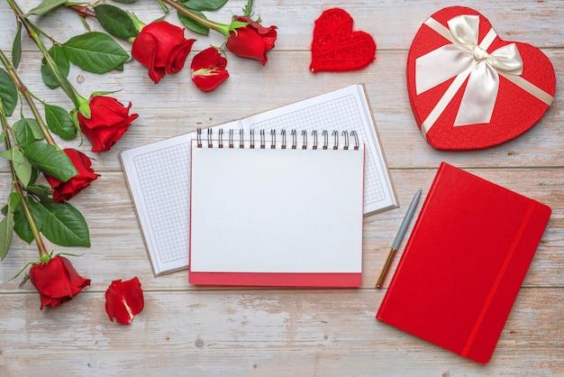 Scatola regalo a forma di cuore di quaderno a quadri con copertina rigida aperta con rose e petali di fiocco in raso