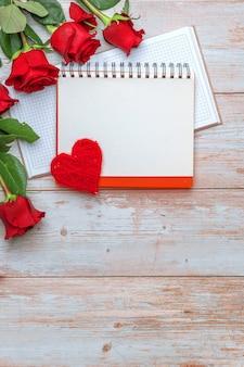 Quaderno con copertina rigida aperto con rose e petali in corda di san valentino con superficie in legno