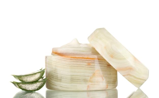 Barattolo aperto di crema e aloe isolato su bianco
