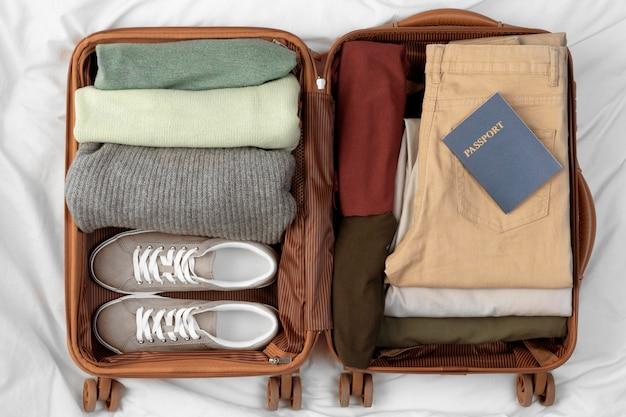 Bagagli aperti con vestiti piegati e passaporto