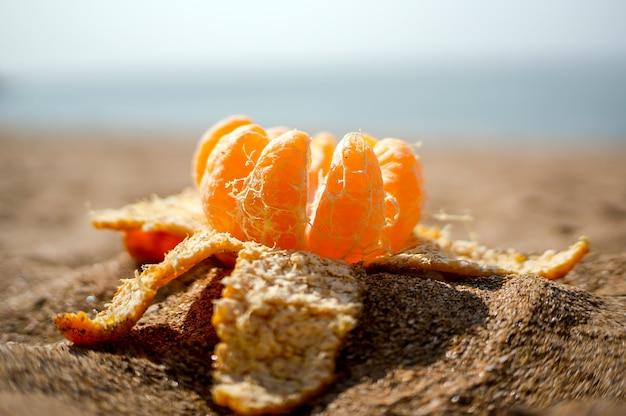 Il mandarino aperto si trova sulla sabbia. l'arancia si è scomposta a fette, su sfondo sfocato mare e spiaggia