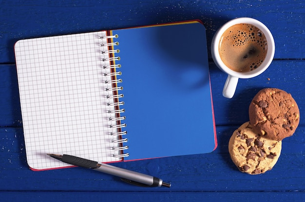 Taccuino aperto, tazza di caffè e biscotti su uno sfondo blu scuro, vista dall'alto