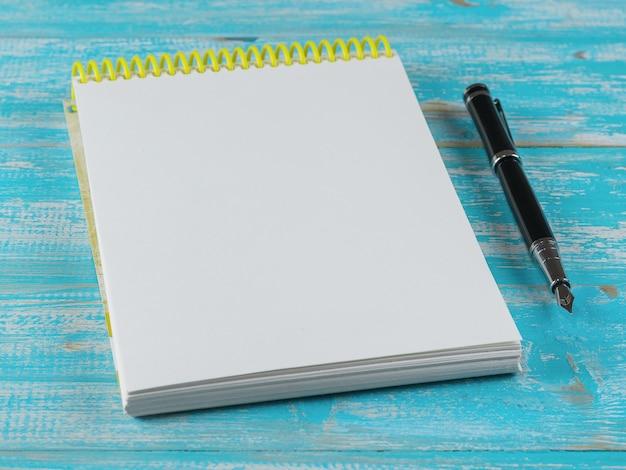 Taccuino aperto con una penna stilografica su una tavola di legno blu