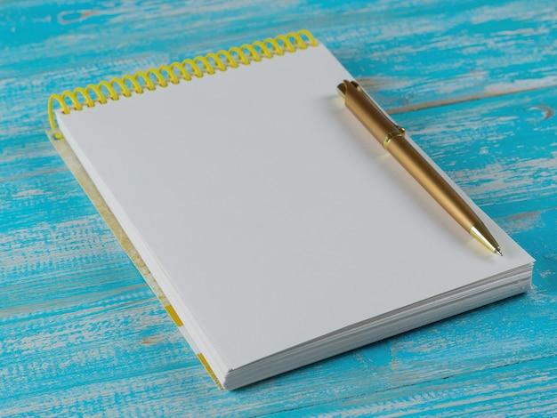 Taccuino aperto con una penna d'oro su un tavolo blu