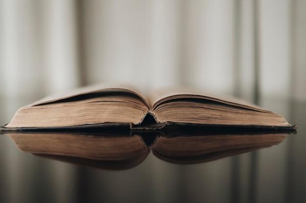 Vecchio libro aperto con riflesso nella superficie marrone