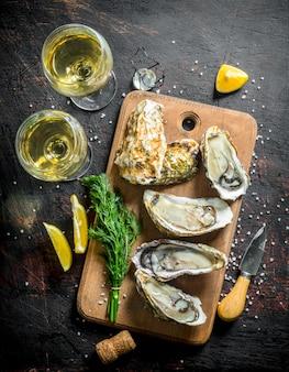 Ostriche aperte su un tagliere con vino bianco, un mazzetto di aneto e fette di limone. su fondo rustico scuro