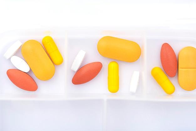 Portapillole aperto con pillole gialle e rosse sul tavolo bianco