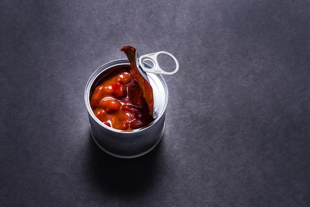 Barattolo di latta aperto, fagioli caldi inscatolati del peperoncino rosso su fondo nero