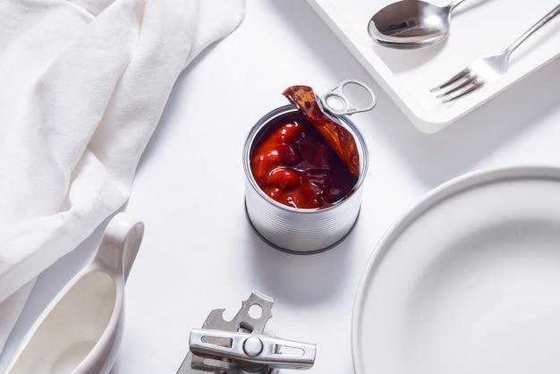 Barattolo di latta aperto, fagioli caldi in scatola del peperoncino rosso sulla tavola bianca