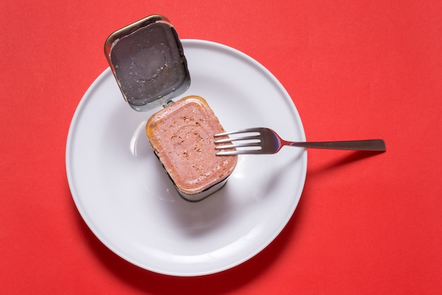 Lattina aperta con carne in scatola, tavolo da cucina vista dall'alto