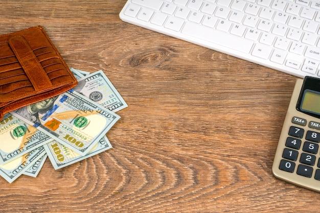 Portafoglio aperto con banconote in dollari e calcolatrice sul tavolo