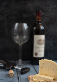 Bottiglia di vino, vetro e formaggio aperti su uno sfondo scuro