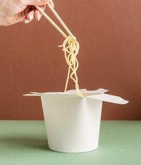 Scatola di carta wok aperta per mock up design. mano della donna che tiene le tagliatelle con le bacchette