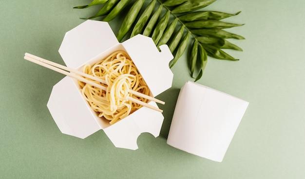 Scatola di carta wok aperta con tagliatelle e bacchette, mock up design vista dall'alto piatto giaceva su sfondo verde