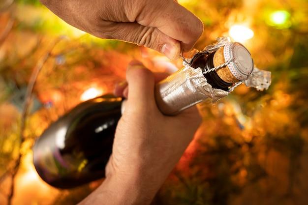 Apertura di una bottiglia di spumante come champagne, mano d'uomo, luci di capodanno, felice anno nuovo e natale, celebrazione