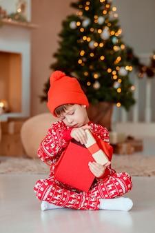 L'apertura del bambino è presente all'albero di natale in casa. ragazzo in pigiama rosso con regali di natale. ragazzino con una confezione regalo e caramelle all'albero di natale. decorazioni per la casa.