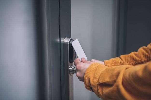 Aprendo la porta. chiuda in su della mano dell'uomo che apre la porta con una carta di accesso