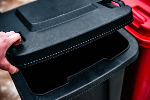 Aprire il coperchio del bidone della spazzatura per buttare la spazzatura.