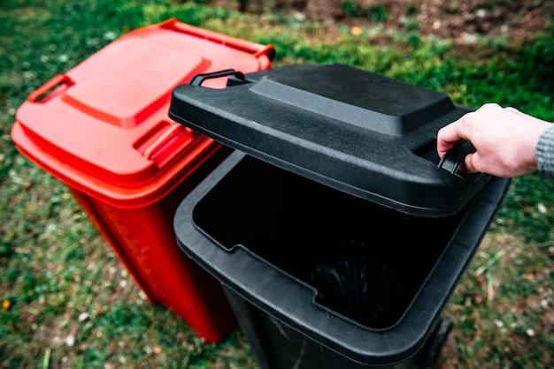 Aprire il coperchio del bidone della spazzatura per buttare la spazzatura. Foto Premium