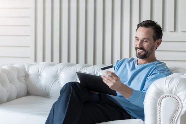 Operazioni con carta di credito. uomo barbuto positivo attraente che si siede su un divano bianco e che tiene un tablet mentre si effettua un pagamento elettronico
