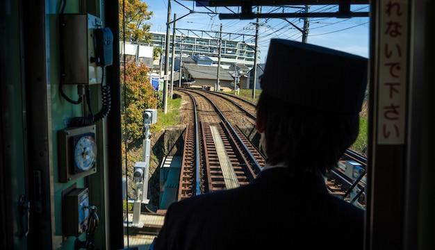 L'operatore sul posto di controllo interno accelera il treno locale giapponese di kyoto per la lunga e la breve distanza, viaggiando su binari lungo la ferrovia. scena ferroviaria e paesaggio di viaggio in giappone