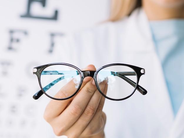 Medico oculista che tiene un paio di occhiali da vista