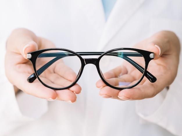 Oculista che mostra un paio di occhiali