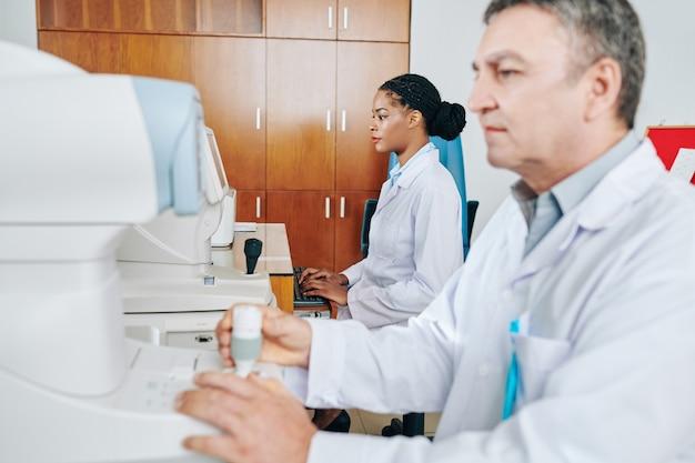 Oculista che lavora su apparecchiature mediche quando il suo assistente lavora al computer e inserisce le informazioni sui pazienti