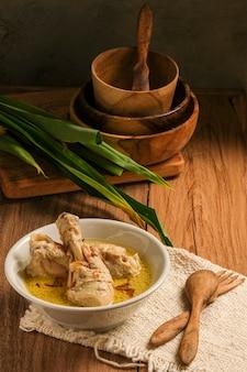 L'opor ayam viene servito su un tavolo di legno. l'opor è un cibo tradizionale indonesiano a base di pollo cotto con salsa al latte di cocco