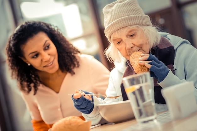 Possibilità di mangiare. piacevole donna senior seduta al tavolo pur avendo una gustosa cena