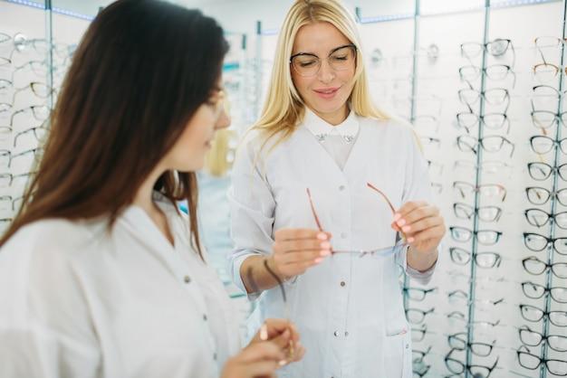 L'ottico mostra gli occhiali al cliente nel negozio di ottica