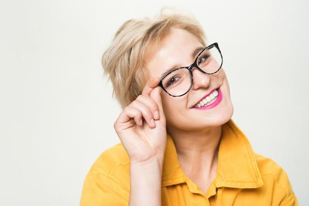 Negozio di ottica. occhiali alla moda. gli occhiali da vista biondi sorridenti di usura della donna si chiudono su. la moda degli occhiali. aggiungi un accessorio intelligente. ragazza alla moda con gli occhiali. vista e salute degli occhi. buona visione