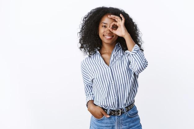 Ottimista affascinante giovane donna afro-americana di 25 anni che indossa una camicetta a righe che mostra ok gesto ok cerchio sull'occhio sorridente guardando attraverso felicemente giocoso, sorridente ampiamente assicurato nessun problema